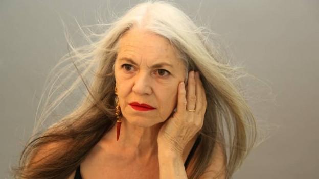 Model mit grauen Haaren um die 60.