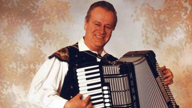 Der Akkordeonist Slavko Avsenik steht mit seinem Akkordeon vor einer braun-weiss gemusterten Tapete.