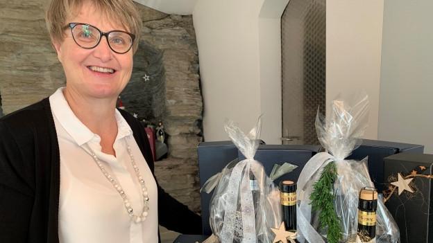 Frau präsentiert festlich geschmückte Weinflaschen.