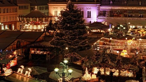 Weihnachtsmarkt mit beleuchtetem Tannenbaum.