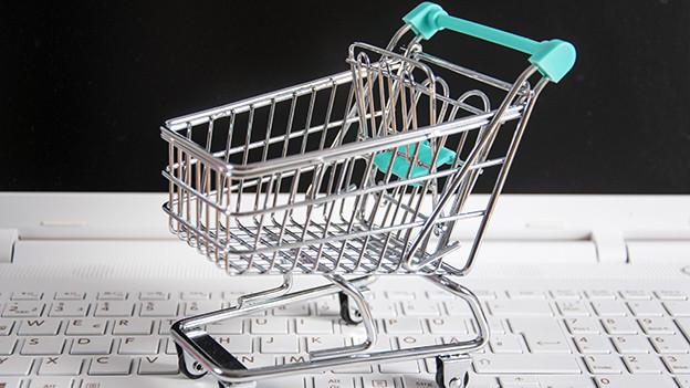 Ein Miniatur-Einkaufswagen auf einer Computer-Tastatur.