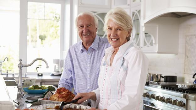 Älterer Mann und ältere Frau kochen zusammen