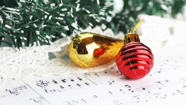 Christbaumkugeln liegen auf Musiknoten.