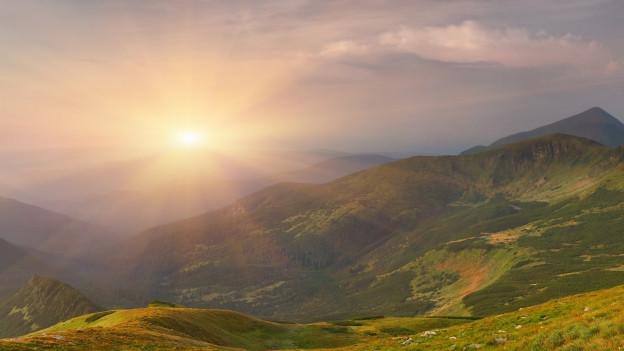 Die Sonne scheint über den Bergen.