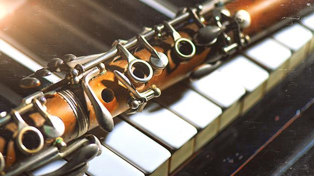 Eine alte Klarinette auf einem alten Klavier.