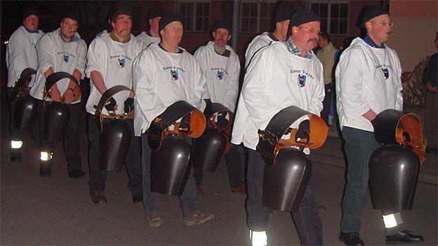 Eine Gruppe von Männer in weissen Hemden mit Treicheln.