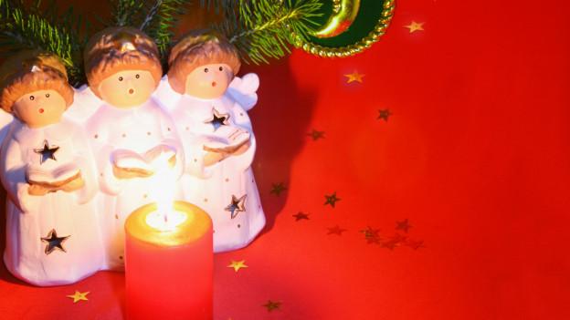 Drei Engelsfiguren singen vor einer brennenden Kerze.