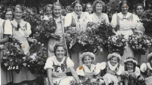 Foto von Frauen und Mädchen in Trachten mit Blumenkränze.