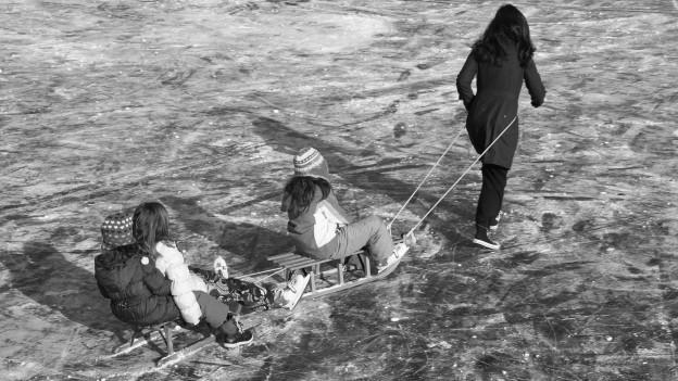 Zugefrorener See. Frau zieht Schlitten mit Kinder übers Eis.