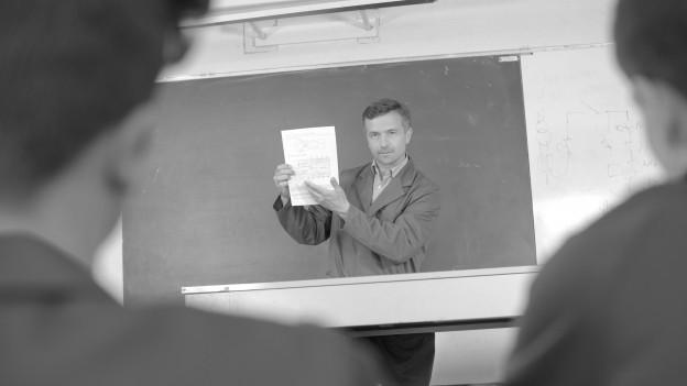 Ein Lehrer erklärt etwas im Schulzimmer.