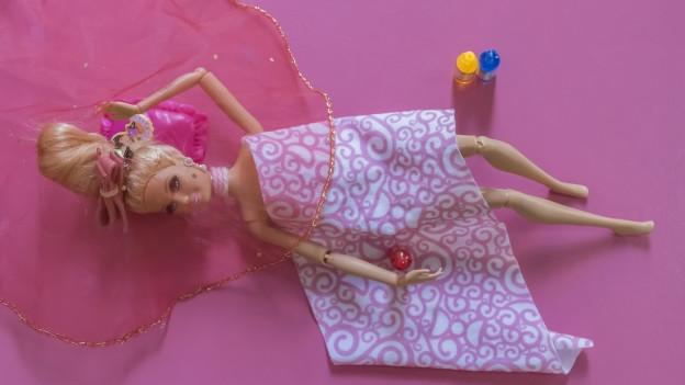 Eine Barbie-Puppe liegt auf dem Boden.
