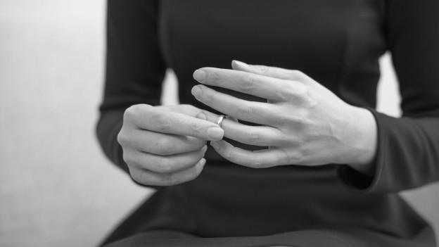 Eine Frau zieht ihren Ehering aus.