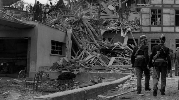 Haus liegt in Trümmern. Soldaten gehen daran vorbei.