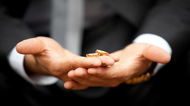 Zwei Eheringe auf der Hand eines Mannes.