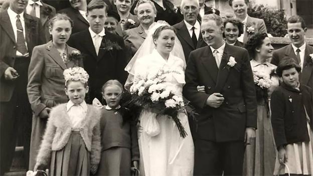 Schwarz-Weiss-Fotografie von einer Hochzeits-Gesellschaft.