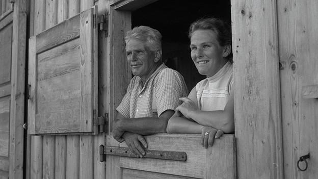 Ein Mann und eine Frau über der halboffenen Stalltür.