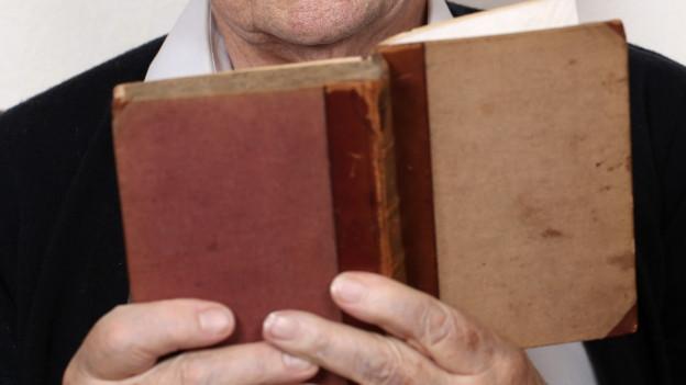 Ein älterer Mann hält ein Buch in der Hand.
