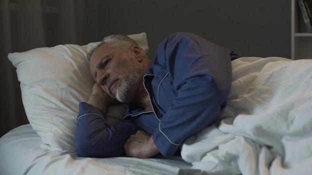 Ein Mann liegt wach in seinem Bett.