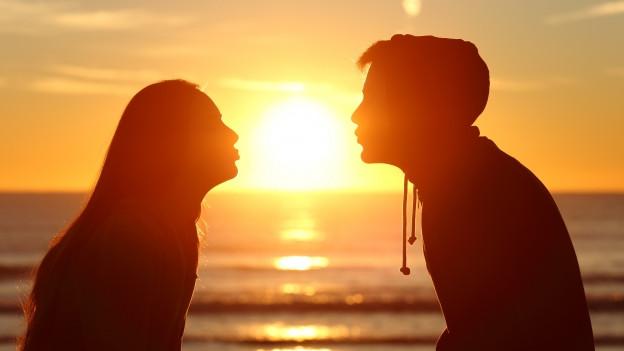 Zwei Jugendliche möchten sich bei Sonnenuntergang am Strand küssen.