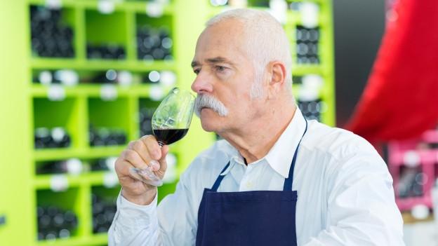 Ein Mann riecht am Wein.