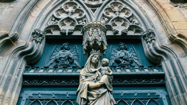 Eine Maria-Figur vor der Kirche.