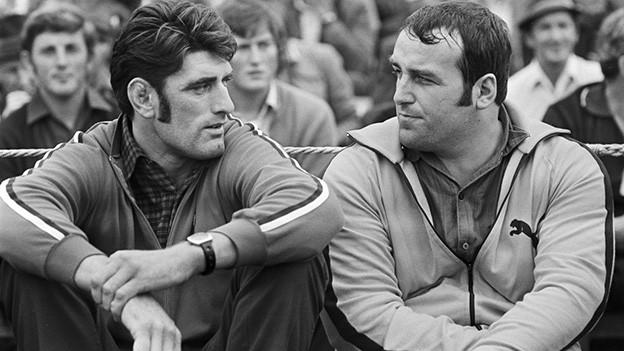Schwarz-Weiss-Fotografie von zwei kräftigen Männern.