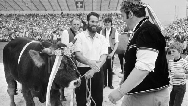 Der Schwinger Rudolf Hunsperger erhält 1974 nach seinem Sieg am Eidgenössischen Schwing- und Älplerfest in Schwyz bei der Siegerehrung einen Muni.