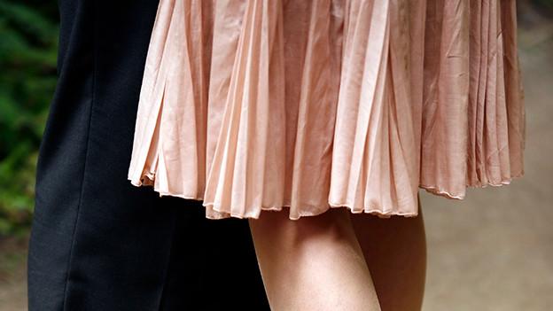 Beine von einem Mann in langen Hosen und einer Frau im kurzen Rock.