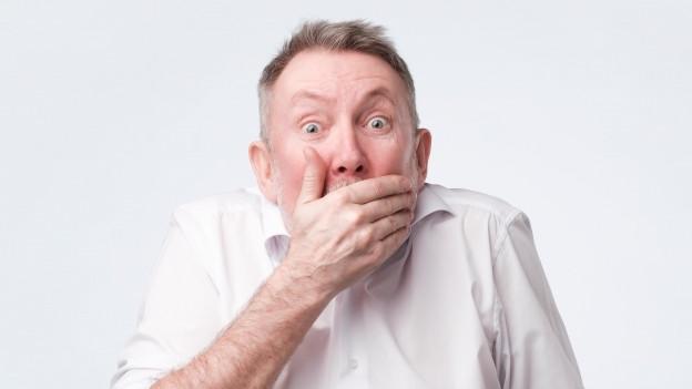 Ein Mann hält sich die Hand vor den Mund.