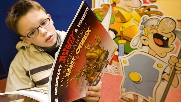 Ein Bub liest eine Ausgabe von Asterix & Obelix.