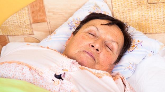 Schlafende Frau auf Bett.