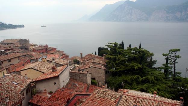 Blick über italienisches Bauerndorf an See.