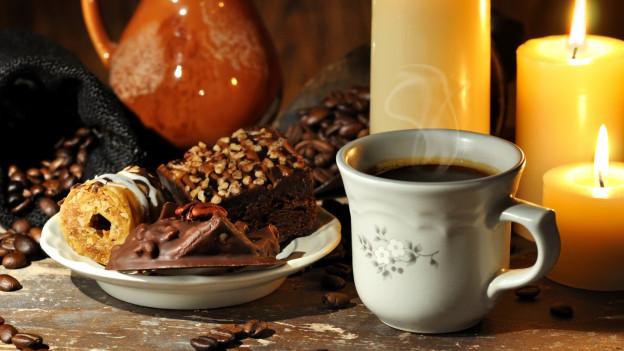Eine Tasse Kaffe mit drei Kerzen und einem Teller Guetzli.