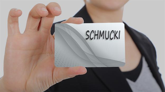Konturen einer Frau, die eine Visitenkarte mit dem Namen Schmucki zeigt.