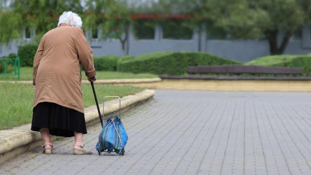 Eine alte Frau geht langsam mit einem Rollköfferli in der Hand.