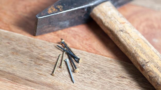 Ein paar Nägel und ein Hammer.