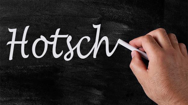 Jemand schreibt mit Kreide das Wort Hotsch auf eine Wandtafel.