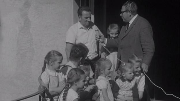 Radioreporter interviewt Mann und Kinder.