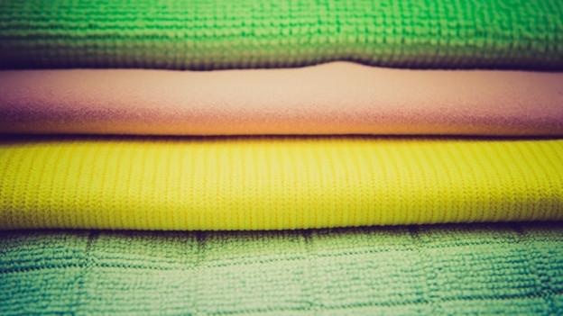 Verschiedenfarbige Tücher liegen auf einem Stapel.