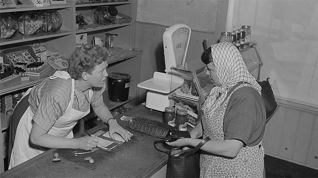 Schwarz-Weiss-Fotografie von Verkäuferin und Kundin in einem Gemischtwarenladen.