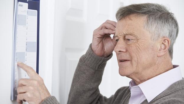 Ein Mann schaut auf den Kalender.