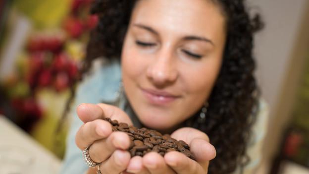 Frau riecht an Kaffeebohnen