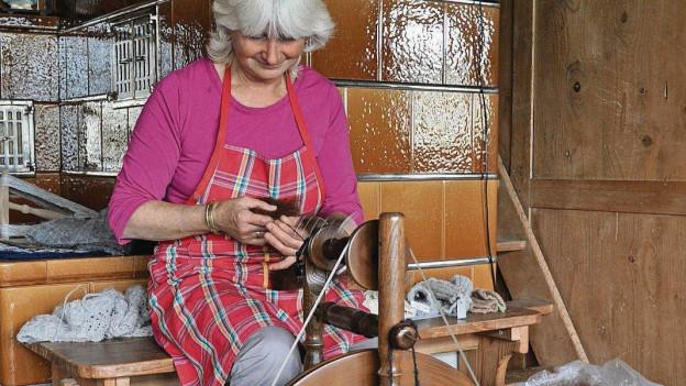 Frau spinnt Wolle.