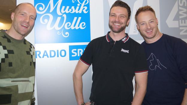 Drei Herren vor Musikwelle Logo.