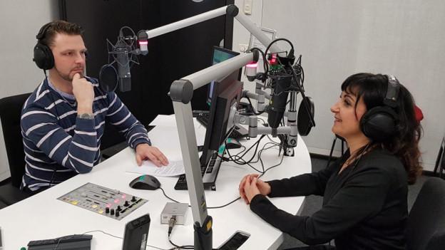 Moderator interviewt Gast im Aufnahmestudio.