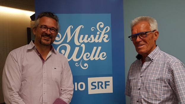 Dani Häusler und Peter Fässler stehen vor dem SRF Musikwelle Logo.