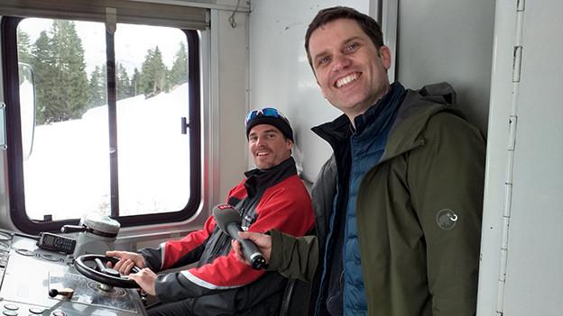 Ein Lokomotivführer und ein Reporter in einer Führerkabine.