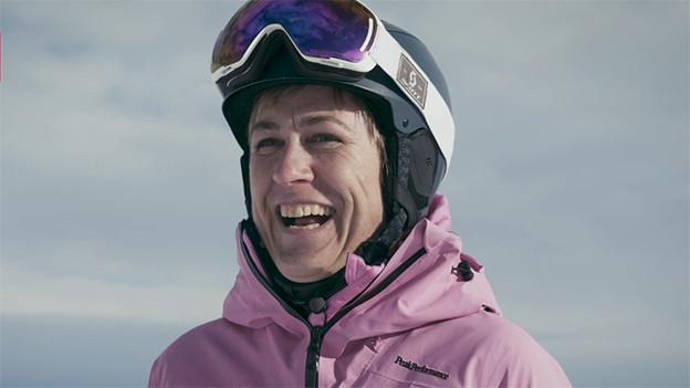 Eine lachende Frau in Ski-Ausrüstung.