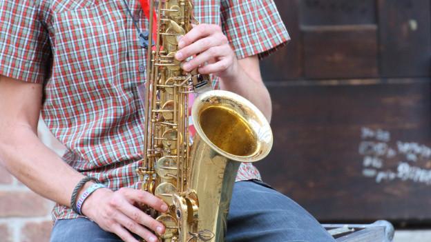 Ein Mann spielt vor einem Haus Saxofon.