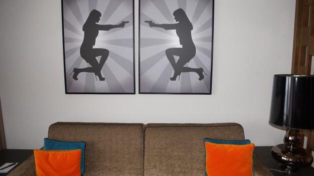 Ein Sofa mit orangen Kissen und Bilder mit Bond-Girl an der Wand.